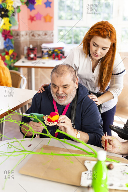 Disabled man doing craft with female caregiver in rehabilitation center