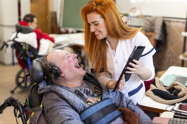 Smiling nurse showing digital tablet to happy disabled man in nursing home