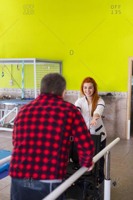 Smiling female nurse motivating disabled man in walking at rehabilitation center