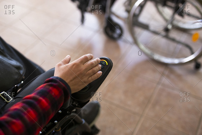 Disabled man's hand on button of motorized wheelchair