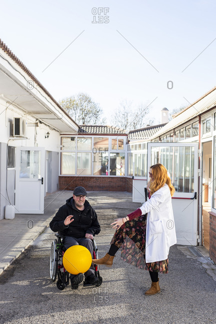 Disabled man and female nurse playing with ball outside rehabilitation center