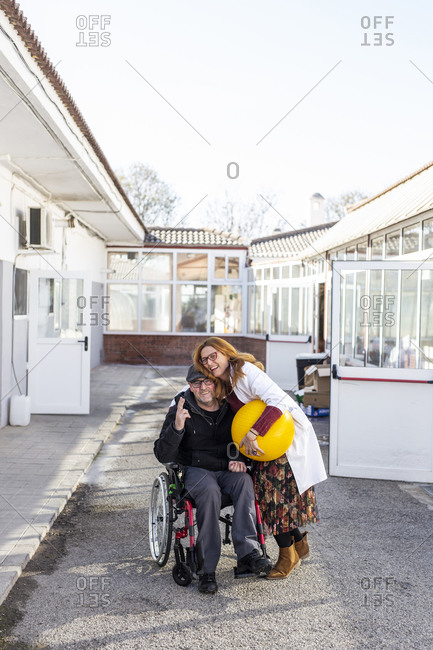 Female healthcare worker embracing disabled man outside nursing home
