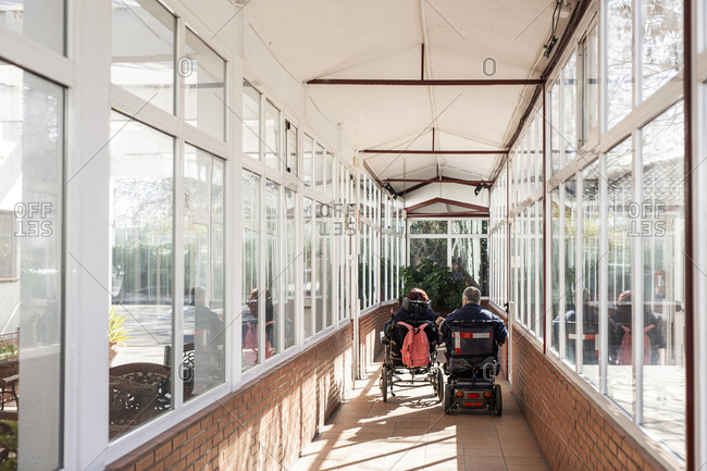 Disabled male and female on wheelchair in corridor at nursing home