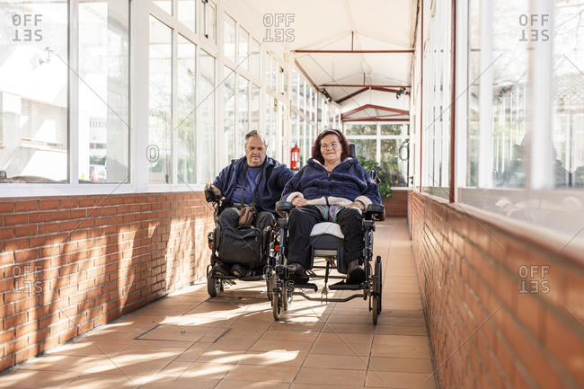 Disabled man and woman on wheelchair in corridor