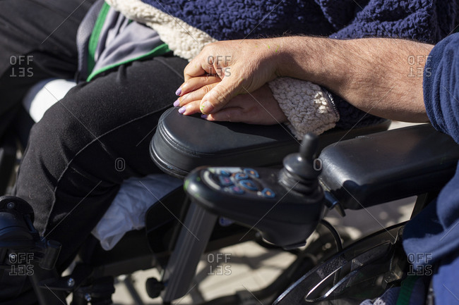 Disabled woman and man holding hands while sitting on wheelchair