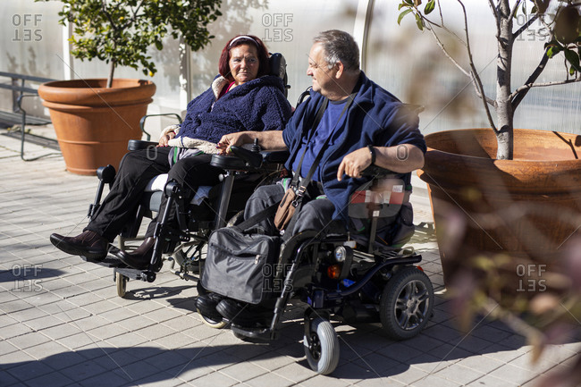 Disabled woman and man holding hands while sitting on wheelchair during sunny day