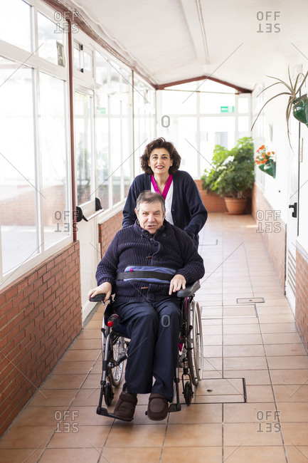 Smiling female caregiver assisting disabled man sitting on wheelchair in corridor