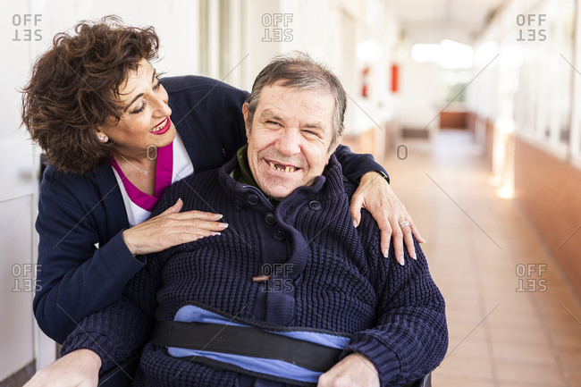 Happy nurse looking at disabled man in corridor of nursing home