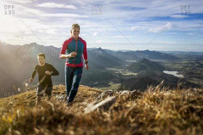 Sports people practicing trail running on mountain path of Saulingspitze at Bavaria- Germany