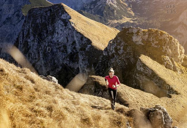 Female athlete running on Aggenstein mountain at Bavaria- Germany