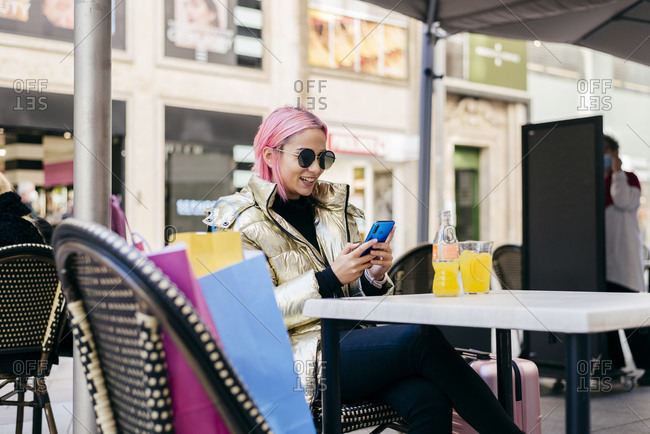 Woman smiling while using mobile phone sitting at sidewalk cafe