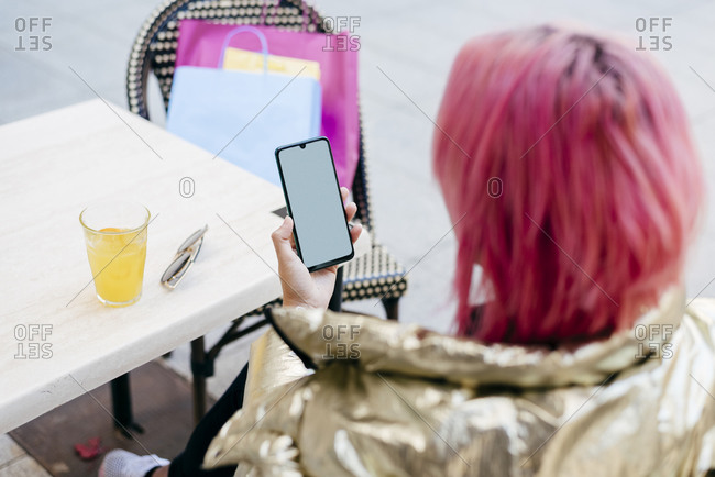 Young woman using smart phone while sitting at sidewalk cafe
