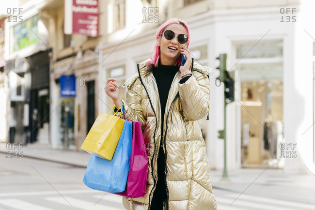 Young fashionable woman with shopping bags talking on mobile phone while standing in city