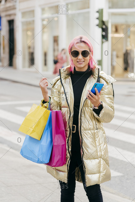Smiling woman carrying shopping bags while using mobile phone standing in city