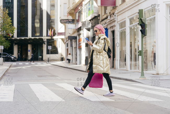 Young woman with shopping bag using mobile phone while walking on road