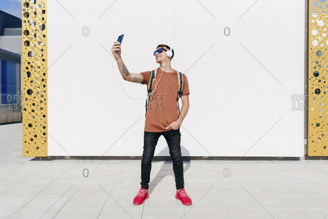 Smiling man wearing headphones taking selfie through mobile phone while standing with hands in pockets against wall