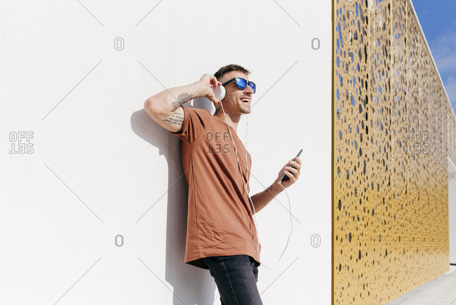 Happy man with mobile phone listening music through headphones while leaning on wall