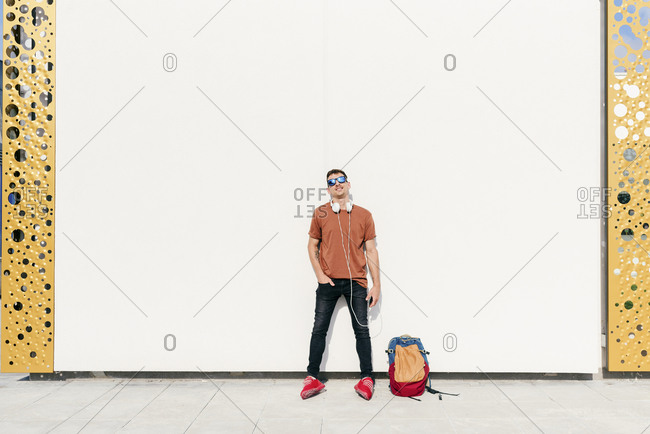 Man with backpack and headphones standing with hands in pockets against wall