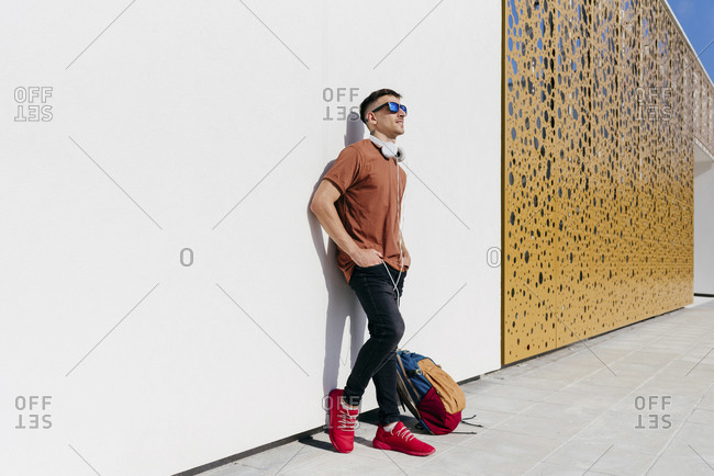 Man wearing sunglasses standing with hand on hip against wall