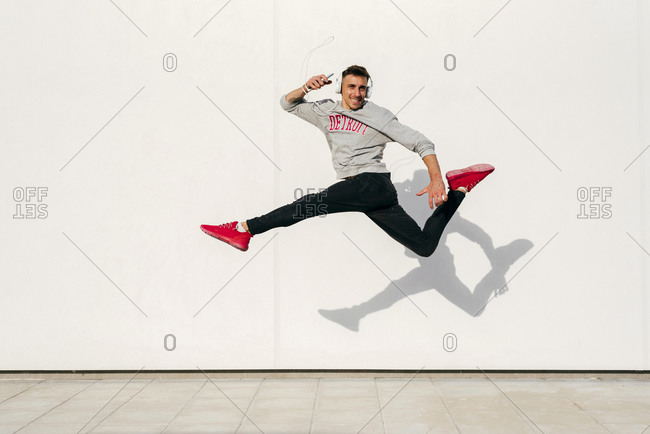 Carefree man wearing headphones holding smart phone while jumping against wall