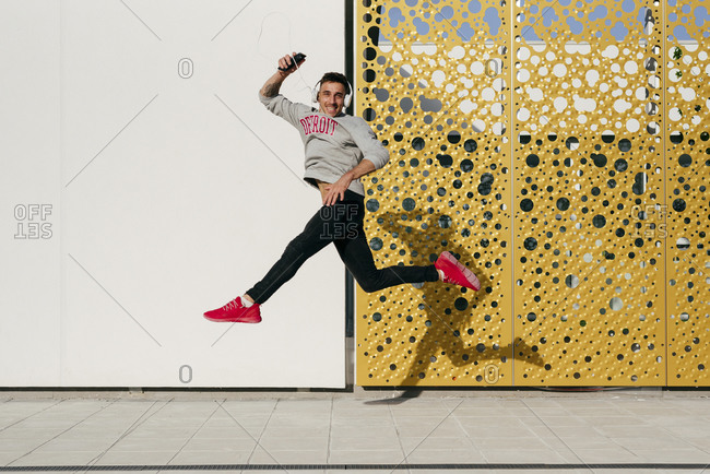 Carefree man with headphones and mobile phone jumping against wall