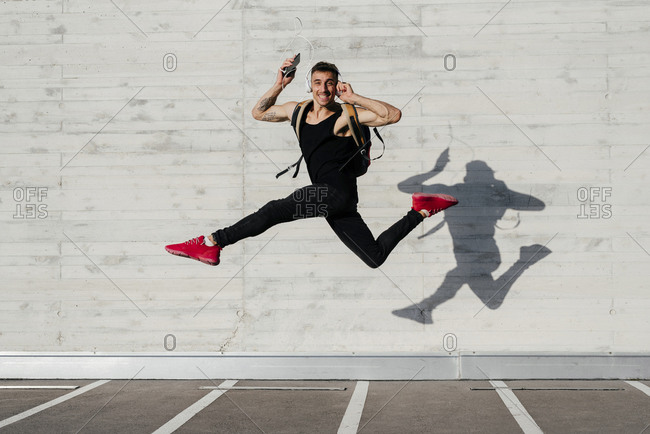 Carefree young man with mobile phone and headphones carrying backpack while jumping against wall