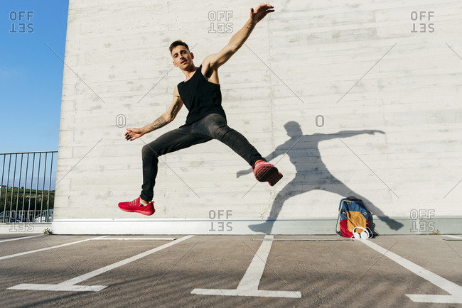 Young man with arms outstretched jumping on footpath during sunny day