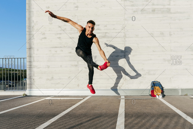 Young man dancing on footpath during sunny day