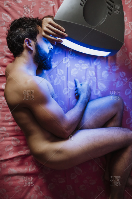 Naked man lying on bed by old television in bedroom