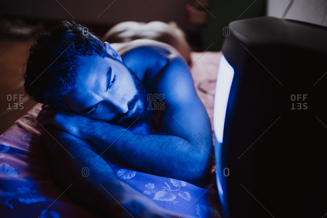 Young naked man looking at old television while lying on bed