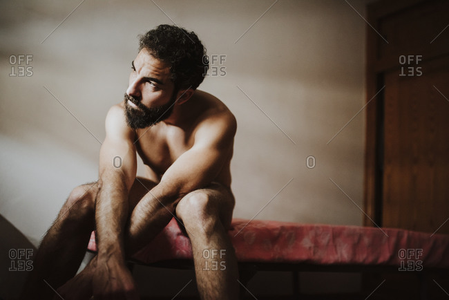 Thoughtful naked man looking away while sitting on bed