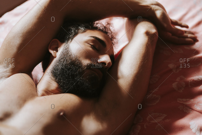 Shirtless man relaxing on bed