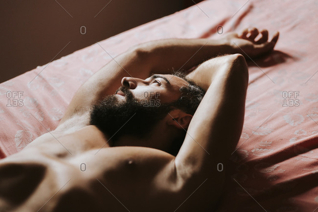 Young shirtless man resting in bedroom at home