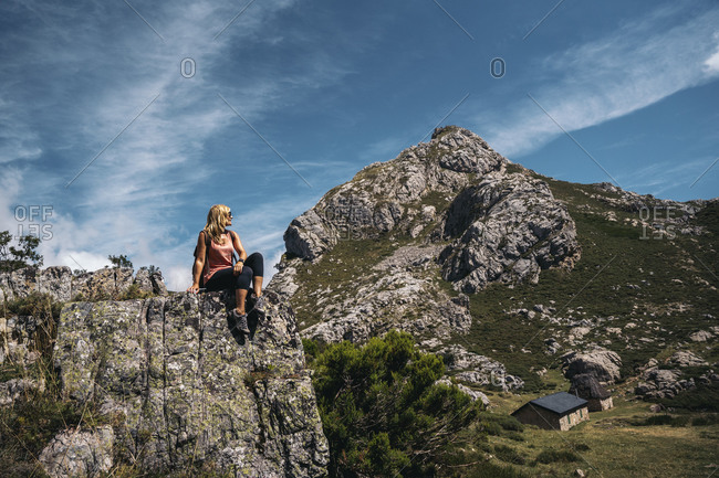 Woman looking away while sitting on rock mountain during sunny day