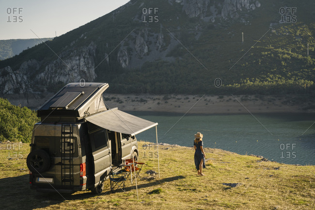 Woman looking at lake while standing by camper van during vacation