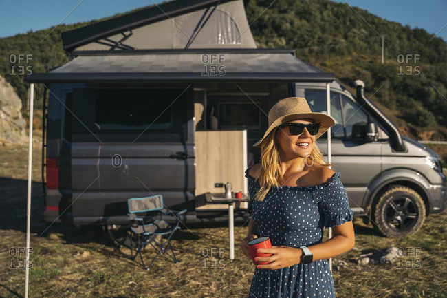 Smiling woman with coffee cup looking away against motor home on sunny day