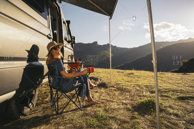 Happy woman in sunglasses with coffee cup laughing while sitting by motor home during vacations