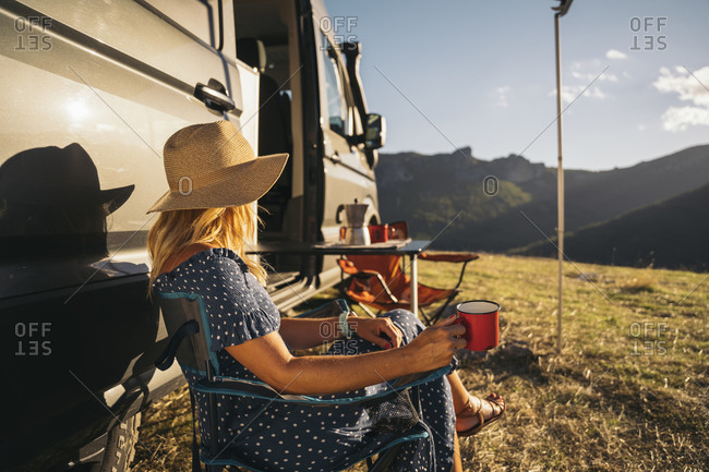 Mid adult woman wearing hat having coffee by motor home on sunny day