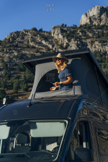 Happy woman with hat leaning out from rooftop of camper van on sunny day during vacations