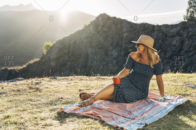 Smiling woman with coffee cup day dreaming while sitting on picnic blanket on sunny day