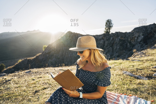 Happy woman reading book while sitting on picnic blanket against mountains on sunny day
