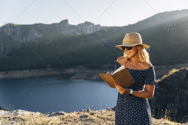 Smiling woman in hat writing in diary against lake on sunny day during vacations