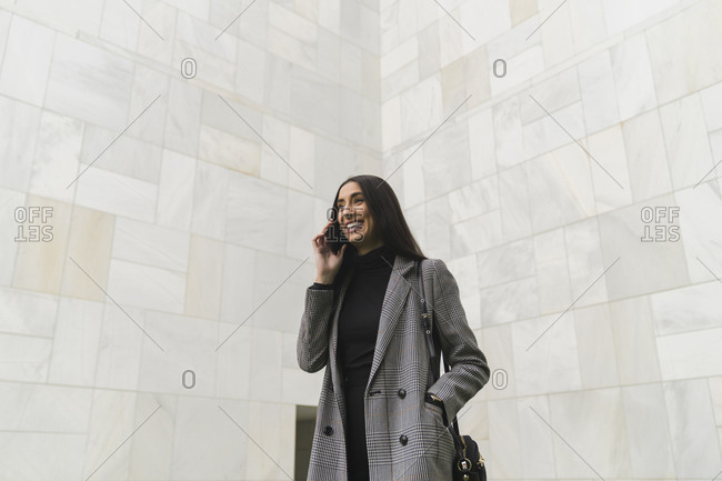 Smiling businesswoman with hands in pockets talking on mobile phone against wall