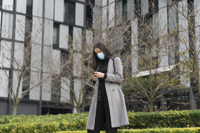 Fashionable female professional in face mask using mobile phone against office building