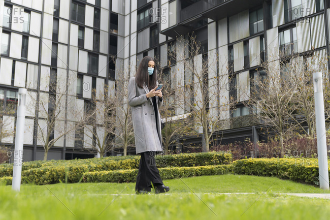 Fashionable female entrepreneur using mobile phone while walking in office park during COVID-19