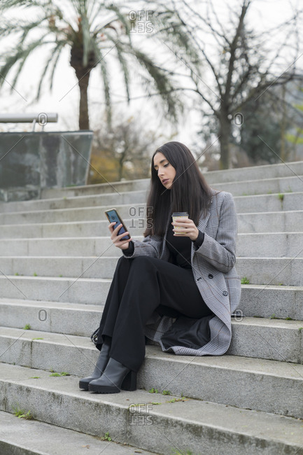 Fashionable businesswoman using mobile phone while having coffee on staircase