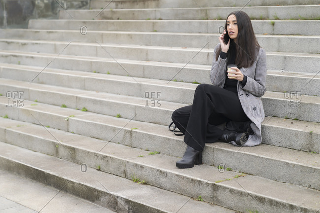 Female entrepreneur with reusable coffee cup on phone call sitting on staircase