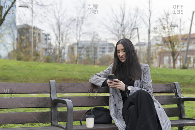 Smiling businesswoman using smart phone on bench at office park