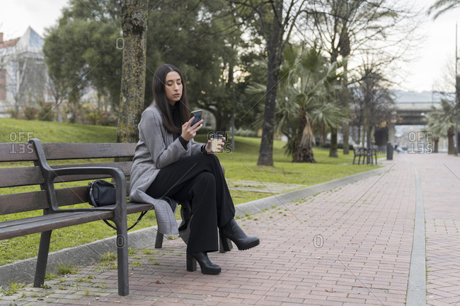 Female entrepreneur using mobile phone while having coffee on bench at office park