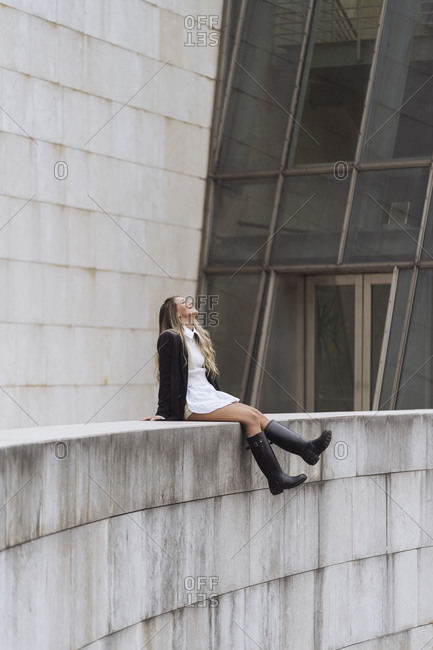 Fashionable businesswoman looking up while sitting on retaining wall of office building